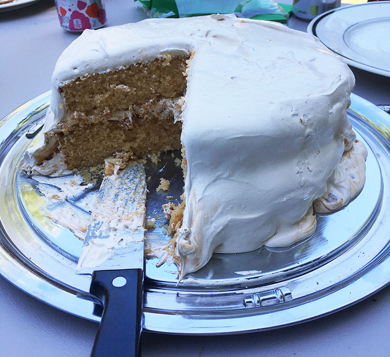 gloopy marshmallow fluff frosting melting off the side of the cake